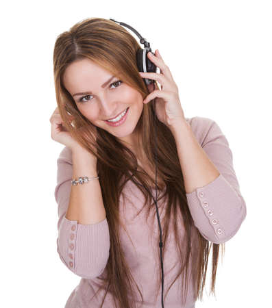 calm background: Young Woman Listening To Music On Headphone Over White Background Stock Photo