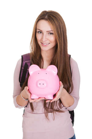 Female Student Holding Piggybank Over White Background photo