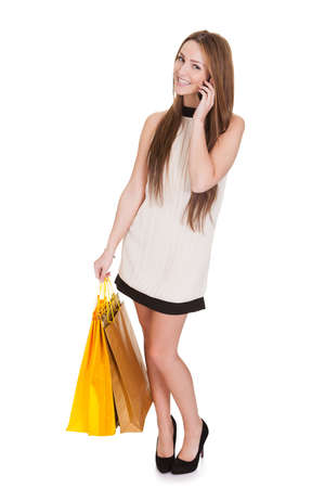 Woman With Shopping Bags Talking On Cell Phone Over White Background photo