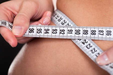 woman measuring: Beautiful Slim Woman Measuring Her Waistline With A Measuring Tape