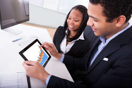 analyst: Businessman And Businesswoman Looking At Digital Tablet Showing Graph