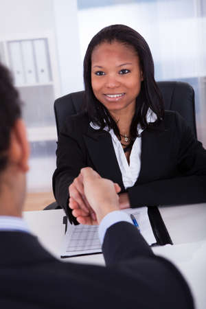 Businesswoman Shaking Hands With Man In The Office photo