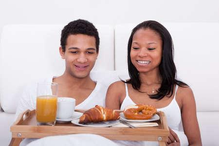 bed and breakfast: Portrait Of African Couple Having Breakfast In Bedroom