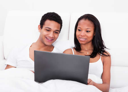 Portrait Of Young African Couple Looking At The Laptop Stock Photo - 19400006