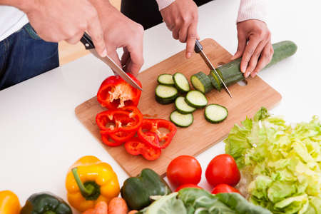 chopping board: Portrait Of Couple Chopping Vegetables In Kitchen Stock Photo