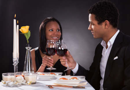 Portrait Of Romantic Couple Toasting Red Wine At Dinner