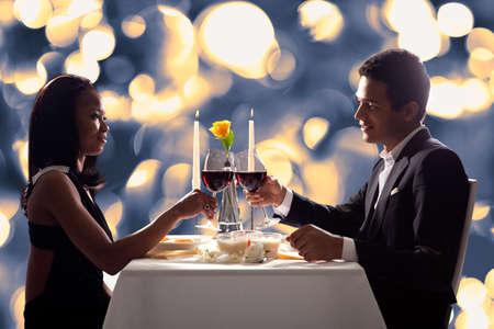 Portrait d'un couple romantique grillant le vin rouge au dîner