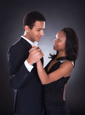 Portrait Of Young African Couple Dancing Over Grey Background photo