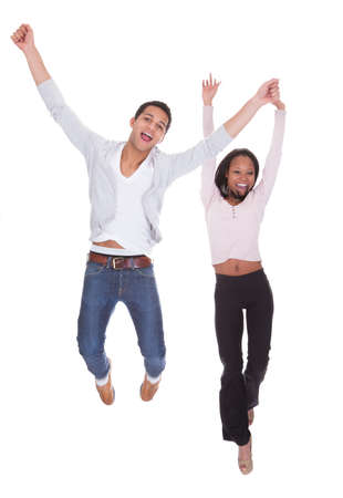 Young Couple Jumping In The Air Over White Background photo