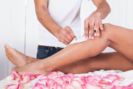 depilation: Close Up Of Woman Legs Waxed In Spa Stock Photo