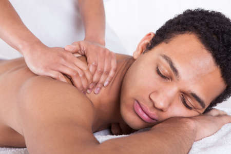african american spa: Portrait Of Man Receiving Massage Treatment From Female Hand Stock Photo