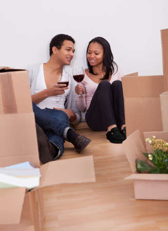 Portrait Of Couple Unpacking Boxes And Drinking Wine In House Stock Photo - 19524443