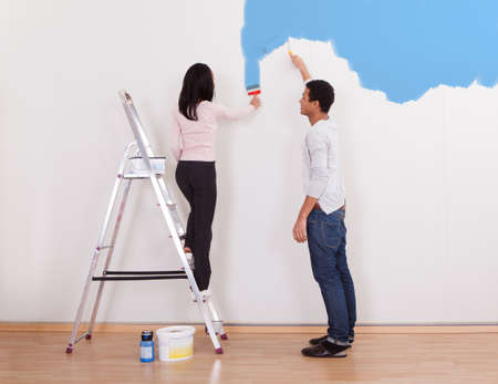 Portrait Of Young Couple Painting The Wall In The Apartment photo