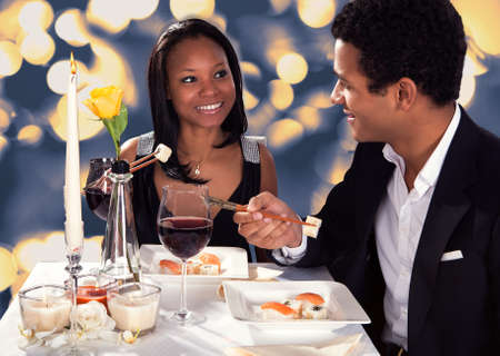 have on: Portrait Of Romantic Couple Eating Sushi At Dinner Stock Photo