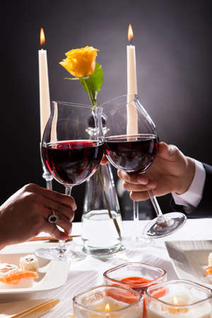 dinner couple: Close -up Of Couple Hands Toasting Red Wine Over Grey Background Stock Photo