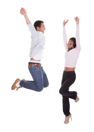 Young Couple Jumping In The Air Over White Background Stock Photo - 19510499