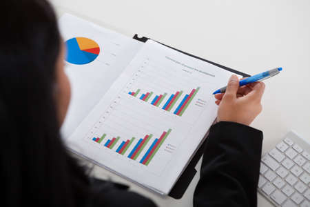Close-up Of Businesswoman Studying Graph In Office Stock Photo - 19632376