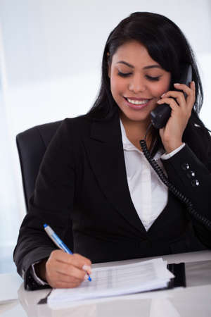 making notes: Young Happy Businesswoman Writing Message From Phone Stock Photo