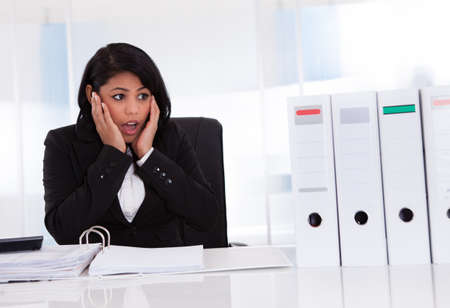 Shocked Businesswoman Looking At Folder In Office Stock Photo - 19632367