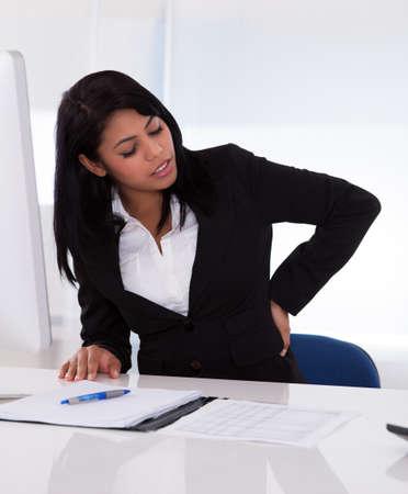 dolor de espalda: Empresaria joven que se sienta en una silla y sosteniendo su espalda en el dolor
