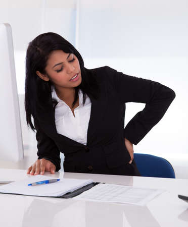 copyspace corporate: Young Businesswoman Sitting On Chair And Holding Her Back In Pain