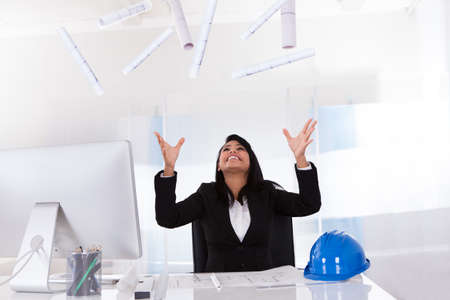Portrait Of Excited Female Architect Celebrating In Office photo