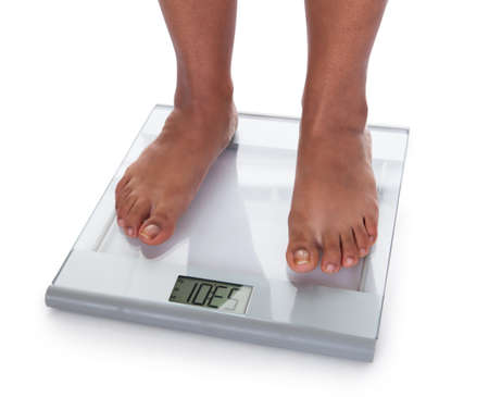 low scale: Low Section Of A Young On A Weighing Scale Against White Background