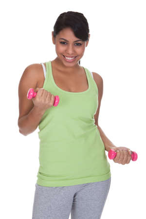woman lifting weights: Young Woman Exercising With Dumbbells Over White Background
