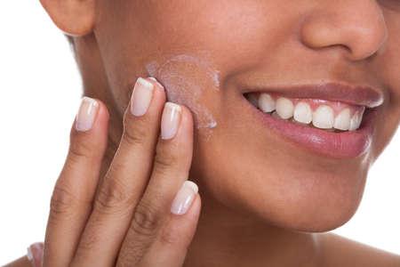 piel humana: Mujer joven aplicar crema en la cara sobre el fondo blanco