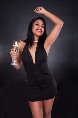 transparent dress: Woman Holding Glass Of Champagne Over Black Background
