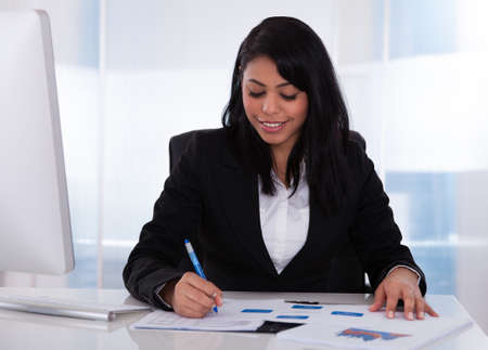 Happy Businesswoman In Office Working On Paper photo