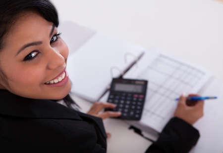 Retrato De La Empresaria Joven Que Hace Cálculos En La Oficina Foto de archivo