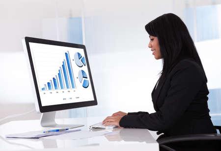 Retrato De La Empresaria Gráfico Analizando en el ordenador