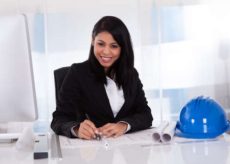 female architect: Portrait Of Female Architect Drawing Blueprint In The Office