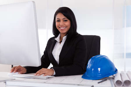 Happy Young Female Architect Using Computer In Office Stock Photo - 19791919