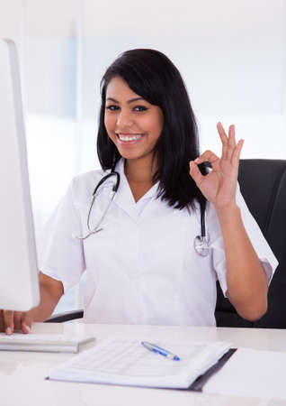gesturing: Happy Female Doctor Using Computer And Gesturing Ok Sign