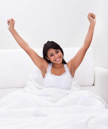 armpit: Joven mujer feliz que estira sus brazos en cama