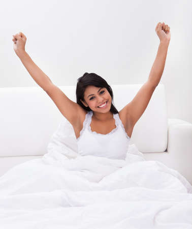 Young Happy Woman Stretching Her Arms On Bed Stock Photo - 19792070