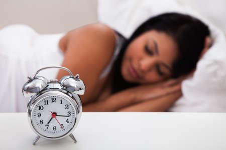 durmiendo: Retrato de la mujer joven que duerme con la alarma de lado Foto de archivo
