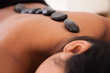 black women naked: Young Woman Getting Spa Treatment With Stone Massage