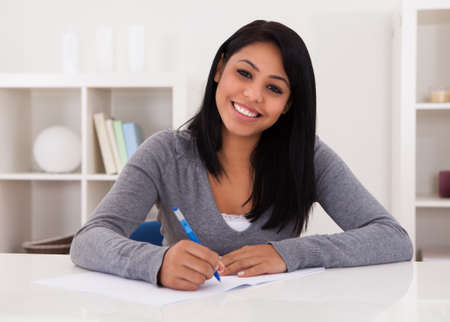Portrait Of Young Happy Woman Writing On Paper photo