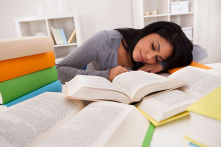Portrait Of Young Woman Sleeping While Studying At Home photo