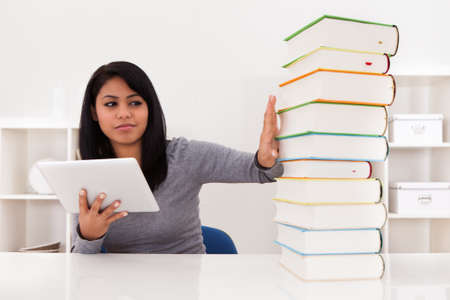Young Woman Avoiding Books And Using Tablet At Home photo