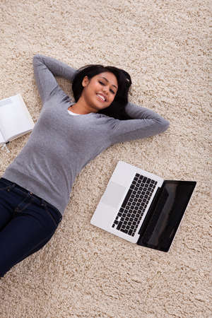 Top View Of Young Woman Lying On Carpet With Laptop photo