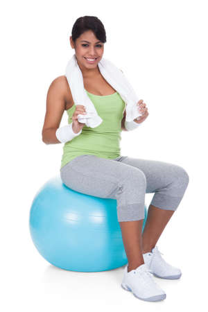 Woman Sitting On Pilates Ball Over White Background photo