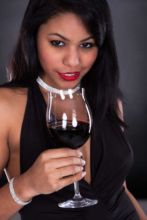 Woman Holding Glass Of Wine Over Black Background photo