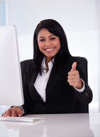 african business: Young Businesswoman Working In Office And Showing Thumb Up Sign Stock Photo