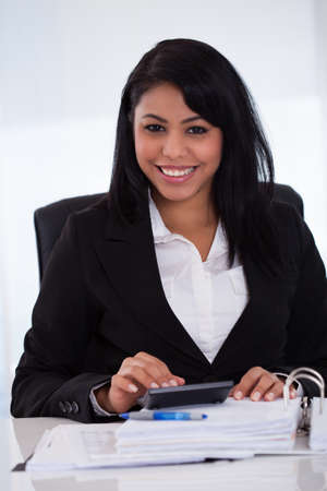 account executives: Portrait Of Young Businesswoman Doing Calculations In The Office Stock Photo