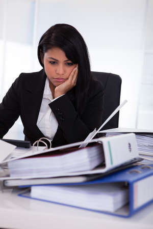 african business woman: Portrait Of Overworked Businesswoman Looking At Folder