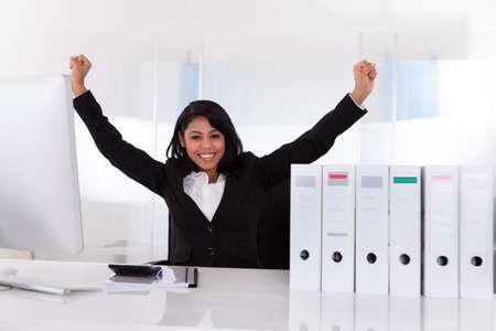 Portrait Of Happy Businesswoman With Hand Raised photo